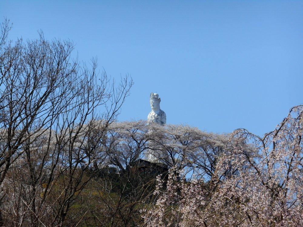 Statue of Funaoka Goddess of Peace on top of the hill, and blooming cherry trees
