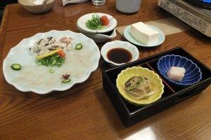 ในจานกลมใบใหญ่ซาซิมิเนื้อปลาปักเป้า เมนูเด็ดของร้าน ส่วนในกล่องสีดำเป็นหนังปลาแช่น้ำส้มสายชูและมันปลาปักเป้า