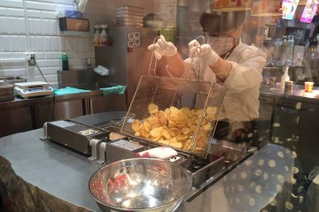 <p>Peeking through the glass window, attentively watching them prepare freshly fried potato chips. Get them while they&#39;re hot!</p>