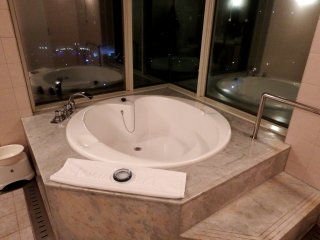 Heart-shaped bathtub with glass window overlooking the lit-up Great Akashi Strait Bridge