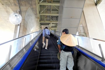 <p>Going up the escalator to the Maiko Highway Bus Terminal, which is located at the foot of the Great Akashi Strait Bridge. It&#39;s directly connected to JR Maiko Station. The man from whose neck the bamboo hat is hanging must be a pilgrim heading for Tokushima in Shikoku</p>