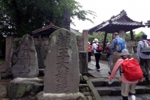 Pilgrims walk past the entrance to a Daikannon temple