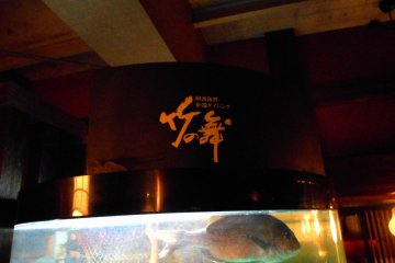 <p>Signage of &#39;Take-no Mai (Bamboo Dance)&#39; and swimming fish in the tank</p>