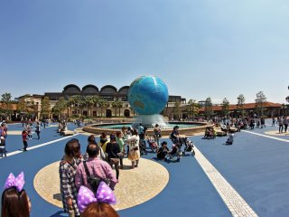 The front of the park has the world globe as a fountain and you can see the entrance to the park in the background.