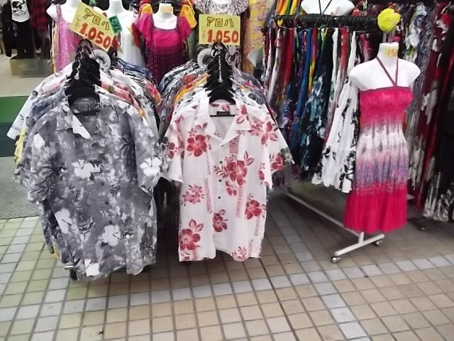 There are lots of colorful shirts and dresses for sale