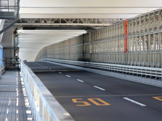 Cars have their own lanes, as do pedestrians who walk the bridge, and the trains are also on the same level on the right side.