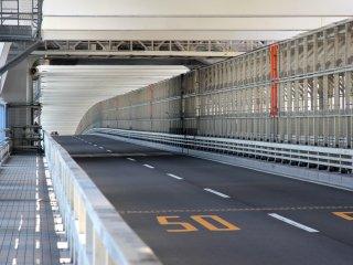 Les piétons, les voitures et les trains ont chacun une voie sur le pont. Sur la photo, à gauche la voie des piétons, au mileu celle des voitures et à droite celle des trains.