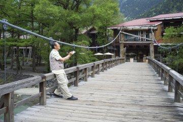 <p>A visitor sketching the beauty of the Hokata mountain range at the Kappabashi bridge</p>