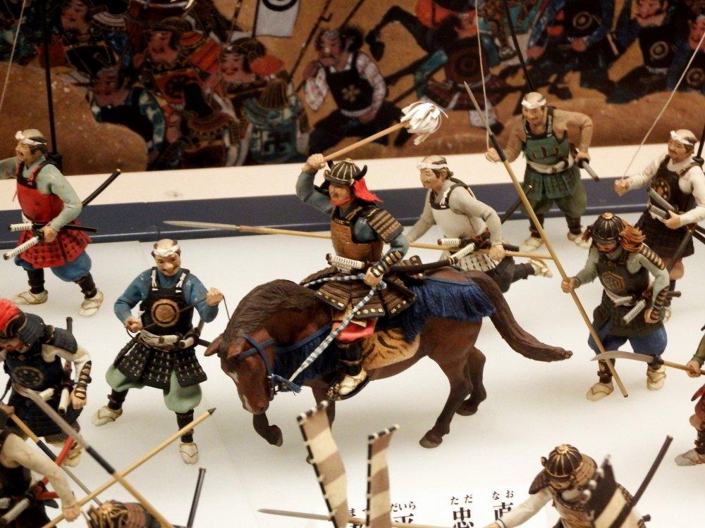 Samurai dengan kostum biru adalah Matsudaira Tadanao, yang berjuang untuk Keshogunan Tokugawa