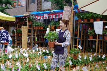 <p>Florist calling shoppers to her stall</p>