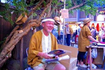 <p>Man giving out fans at Iriya Kishimojin&nbsp;Temple</p>