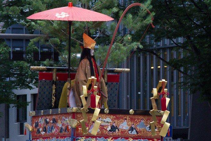 Urade-Yama (占 出山) Trong suốt lễ diễu hành Yamaboko Junko (山鉾巡行) ở Kyoto, 2012! Chiếc kiệu này miêu tả một câu chuyện nổi tiếng khi Hoàng hậu Jingu, một nữ anh hùng huyền thoại chứ không phải là nữ anh hùng lịch sử của Nhật Bản, đi câu cá Ayu (cá ngọt) khi cô ở Hizen (quận Saga ngày nay ở phía bắc Kyushu) để làm một lá số tử vi về chiến thắng hay thất bại của  Hoàng đế
