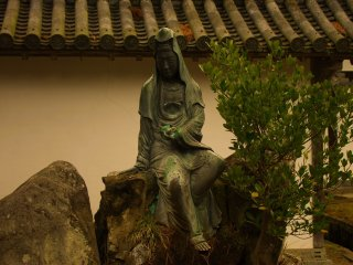 Outside in the front garden of the temple, a statue sits silently