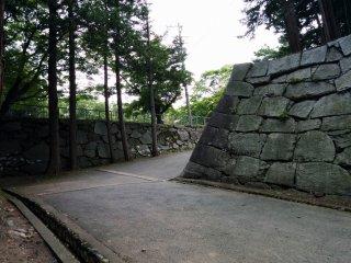 Những bức tường phía sau thành cổ nằm bên sườn con đường bê tông