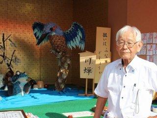 金津町六日区本陣の飾り物を仕切る稲田信夫さん。陶器の小皿を使い、カワセミと魚の鳥獣戯画のような場面を描いている