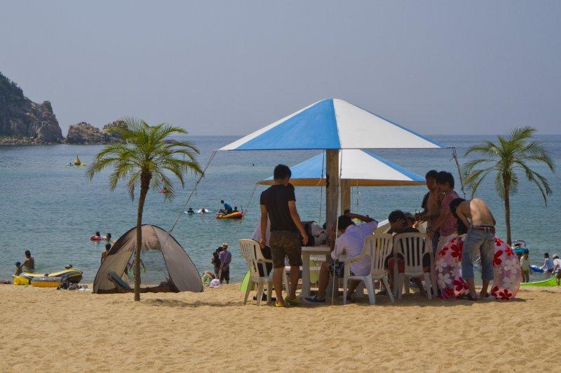 비치하우스들은 해변에 큰 파라솔과 앉을 곳을 제공한다.