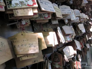 These wooden prayer plaques, known as ema, are used by Shinto worshippers to record their prayers or desired wishes. All of the plaques have maneki neko designs painted on them in respect to the maneki neko shrine directly behind it.