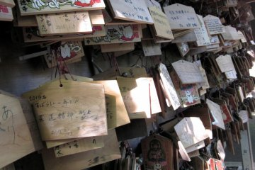 <p>These wooden prayer plaques, known as ema, are used by Shinto worshippers to record their prayers or desired wishes. All of the plaques have maneki neko designs painted on them in respect to the maneki neko&nbsp;shrine directly behind it.</p>