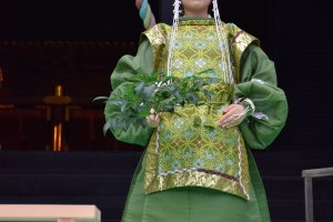 Một nữ thần của đền mặc trang phục đẹp để biểu diễn Kagura với  chồi xanh