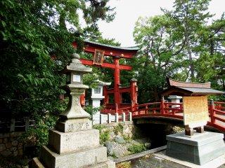 붉은 토리이, 예쁜 다리, 푸른 나무로 둘러싸인 석등이 있는 사당 정문