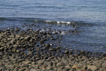 <p>Low lapping sounds among the stones of the shore</p>