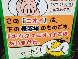 A sign explaining that the smell in the air is not the foxes but the nearby pig farm