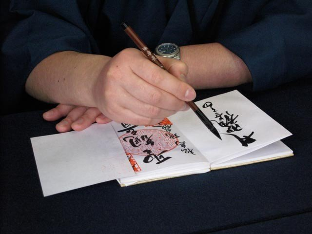 <p>Notice the arm technique by this monk at Asakusa in Tokyo. He supports his writing arm while making sure he does not smear any ink onto stamps from other temples</p>