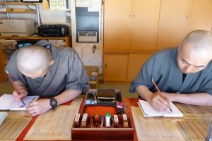 Monks painting goshuinchou across from the large red temple (Konpon Daito) in Koyasan