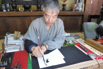 <p>Down the stone path of Koyasan&#39;s Torodo Hall (The Latern Hall) a Monk is busy painting Goshuin Chou</p>