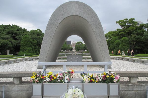 The cenotaph for the A-bomb victims. A chest holds a registry of victims who have passed. The Peace Flame and the A-bomb Dome can be seen through it.