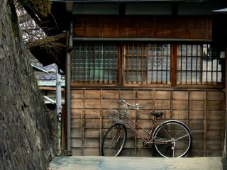 Bicycle leaning against an old wooden house on the way up the hill