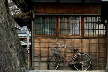<p>Bicycle leaning against an old wooden house on the way up the hill</p>