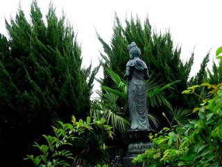 A statue of Kannon peeps between overgrown cypress trees