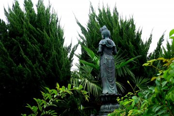 <p>A statue of Kannon peeps between overgrown cypress trees</p>