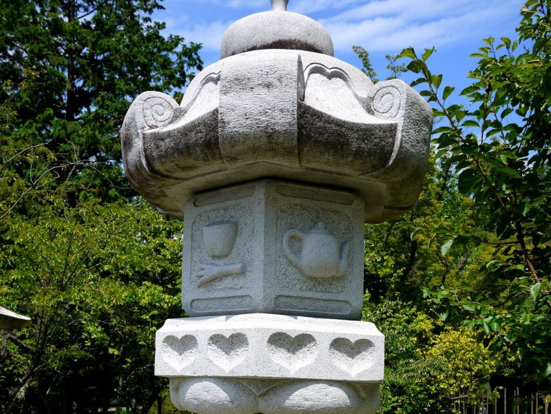 <p>Hearts and a teapot decorate this stone lantern... could it be it an Alice in Wonderland theme?</p>