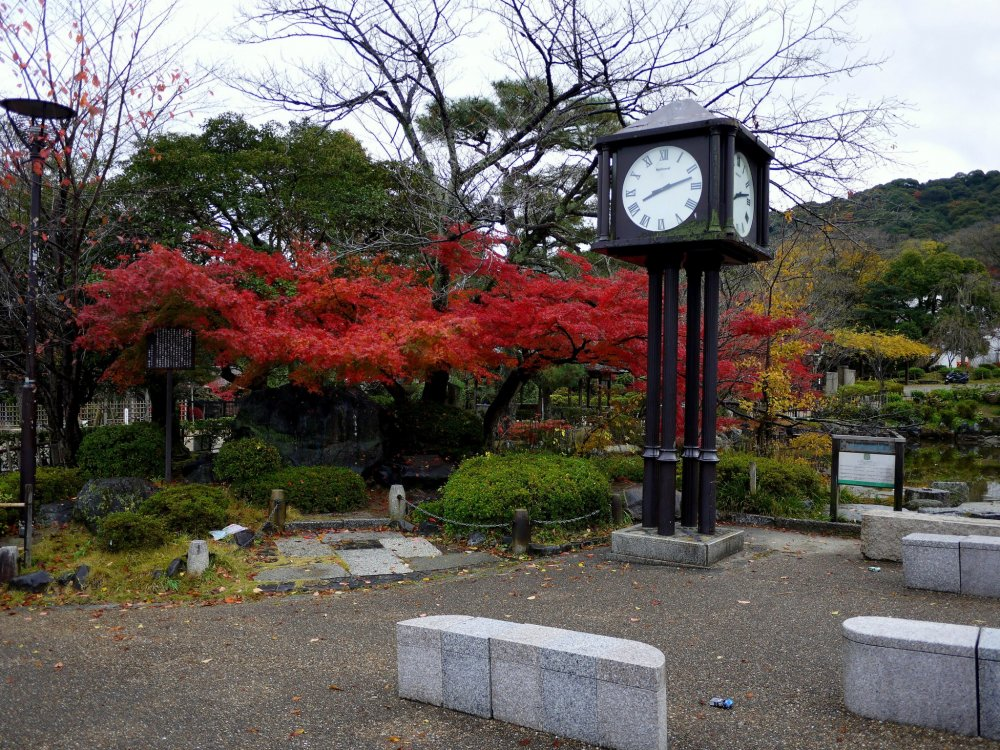 A clock stands in front of a blaze of maple