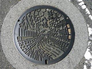 Une bouche d'égout d'Omihachiman montrant le canal sous les cerisiers en fleurs