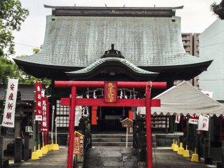 Cổng torii khác nhỏ hơn và đỏ chói đứng trước một cây cầu đá đặc biệt