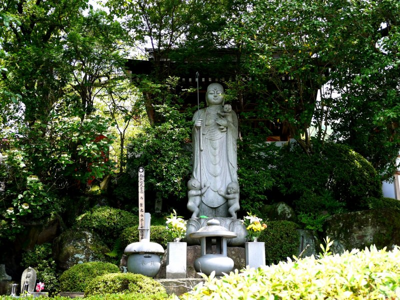<p>Statue with children - perhaps it is Jizo-san, the Buddhist saint who protects children, travelers and firemen</p>