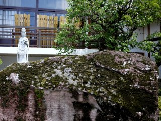 Kanon Statue stands behind a huge rock