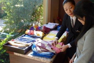 <p>店员正在为客人讲解旅馆内可供使用的浴衣和腰带,她甚至还会帮你安排穿戴呢!</p>