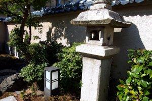 Lentera batu berdiri sendirian di depan kuil