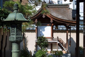 <p>Bronze lantern of Shibata Shrine with Three Sisters Shrine in the backdrop</p>