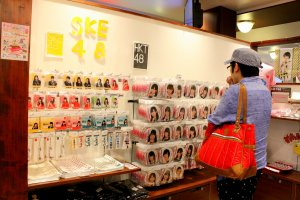 A Japanese AKB48 male fan fancying huge key holders, chains, pins and badges, each bearing the face of a different member of sister groups SKE48 and HKT48