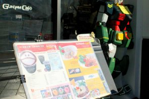 A Gundam robot and a menu welcome each customer to their tiny food shop.