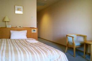 บรรยากาศภายในห้องพักของโรงแรมที่แสนสะดวกสบาย ภายในห้องมีเตียงนอนนุ่มๆ พร้อมมุมนั่งเล่นไว้ให้พักผ่อน และสิ่งอำนวยความสะดวกอื่นๆ อีกมากมาย
