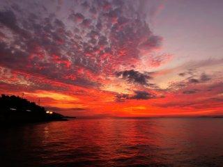เมื่อพระอาทิตย์ตกที่ขอบฟ้า ท้องฟ้าและน้ำทะเลเป็นสีแดงฉาน
