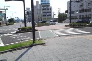 3) Keep walking until you come to a street that merges with yours (it has palm trees down the middle, which are more plentiful if you glance right). Cross it and turn left.