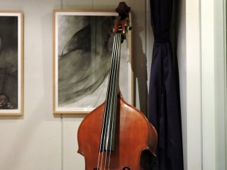 Upright bass guitar propped on the wall in the corner of the gallery