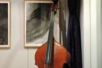 갤러리 코너에 있는 벽에 세워진 베이스 기타